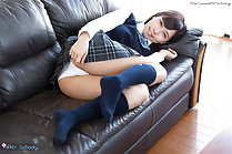 On couch in uniform tugging skirt down panties exposed