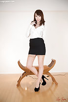 Office lady in white shirt black short skirt high heels standing beside seat