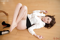 Knees drawn up lying on floor wearing stockings