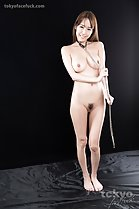Standing naked holding bondage chain over her big breasts trimmed pussy hair bare feet