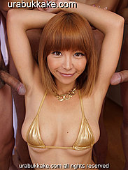 Sumire Kneeling In Front Of Naked Men Arms Raised Above Her Head In Gold Bikini